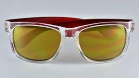 Les lunettes de soleil rouges de boucles d'oreille ont isolé la vue de face photos libres de droits