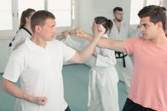 Les mâles adultes et les femelles pratiquent de nouveaux mouvements de karaté dans les paires Photos libres de droits