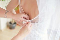 Les mères ou les mains de demoiselles d'honneur aidant avec le ` s de jeune mariée s'habillent Photographie stock libre de droits
