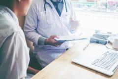 Les médecins et les patients s'asseyent et parlent À la table près de la fenêtre photos stock