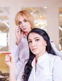 Les médecins féminins s'asseyant à la table et à celle d'entre elles parle o photographie stock libre de droits