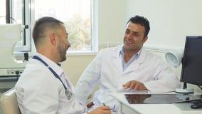 Les médecins heureux discutent quelque chose et rient photos stock