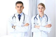 Les médecins se tenant directement avec des bras ont croisé dans l'hôpital Médecins prêts à aider Concept des soins de santé, tra Photo libre de droits