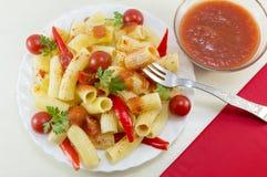 Les macaronis avec les tomates-cerises, le persil et le poivron rouge ont servi l'esprit photographie stock libre de droits