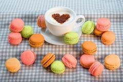 Les macarons colorés avec la tasse de café avec le coeur forment sur le ch Photos stock