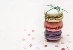 Les macarons colorés avec le petit coeur forment des sucreries sur le fond blanc Images stock