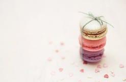 Les macarons colorés avec le petit coeur forment des sucreries sur le fond blanc Photographie stock