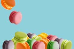 Les macarons colorés durcissent, macaron doux sur le bleu de couleur d'isolement Photographie stock
