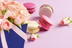 Les macarons dans des couleurs en pastel avec le bouquet des roses roses fleurit Photos stock