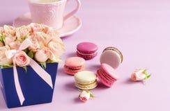 Les macarons dans des couleurs en pastel avec le bouquet des roses roses fleurit Image stock