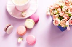 Les macarons dans des couleurs en pastel avec le bouquet des roses roses fleurit Image libre de droits