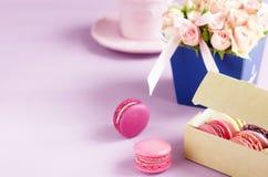 Les macarons dans des couleurs en pastel avec le bouquet des roses roses fleurit Images stock