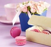 Les macarons dans des couleurs en pastel avec le bouquet des roses roses fleurit Photos libres de droits