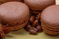 Les macarons et le noir de chocolat ont rôti des grains de café sur le fond jaune Foyer sélectif Image stock