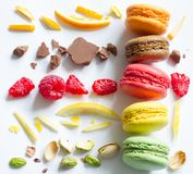 Les macarons français colorés soustraient la vie immobile avec des fruits et des ingrédients sur le fond blanc Photo libre de droits