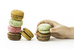 Les macarons français doux et colorés avec la fille remettent se tenir Photographie stock