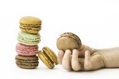 Les macarons français doux et colorés avec la fille remettent se tenir Image stock