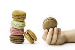 Les macarons français doux et colorés avec la fille remettent se tenir Photo libre de droits