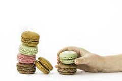 Les macarons français doux et colorés avec la fille remettent se tenir Photo stock