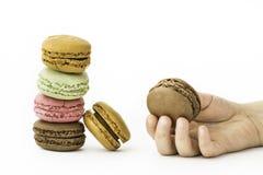 Les macarons français doux et colorés avec la fille remettent se tenir Image libre de droits