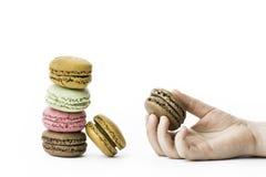 Les macarons français doux et colorés avec la fille remettent se tenir Photos libres de droits