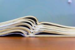 Les magazines ouvertes se trouvent sur l'un l'autre sur une table brune, documents sont en gros plan empilé image stock