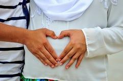 Les mains à un coeur forment sur la bosse de bébé Images libres de droits