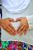 Les mains à un coeur forment sur la bosse de bébé Photographie stock libre de droits