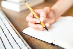 Les mains écrit un crayon lecteur dans un carnet Photos stock