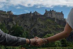 Les mains émouvantes de couples avec Edimbourg se retranchent comme fond Images libres de droits