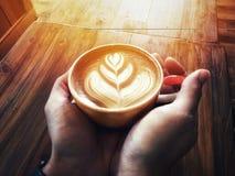 Les mains équipent tenir l'art de Latte de coeur d'amour dans la tasse rouge Image libre de droits