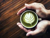 Les mains équipent tenir le thé vert d'art de Latte photographie stock libre de droits