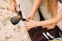 Les mains équipent verse le café turc d'un pot de café en métal dans une tasse et soucoupe blanche, femmes que les mains du ` s a image libre de droits