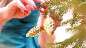 Les mains étroites accrochent le cône de jouet d'or sur le mouvement lent d'arbre de Noël clips vidéos