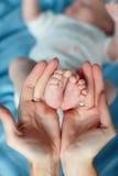Les mains affectueuses du ` s de mère soutiennent doucement le bébé de jambes Photos libres de droits