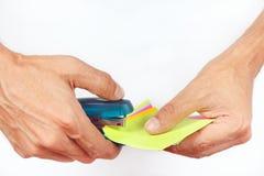 Les mains attachées ont coloré l'agrafeuse de blancs sur le fond blanc Photographie stock libre de droits