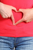 Les mains au coeur forment sur le ventre, symbole de l'amour Photographie stock