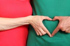 Les mains au coeur forment sur le ventre, symbole de l'amour Images stock