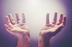 Les mains augmentent avec la paume ouverte, adorent ou prient pour de bonnes choses sous le rayon léger du ciel Image libre de droits