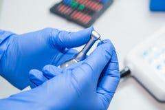Les mains auxiliaires du ` s configure l'équipement dentaire dans le bureau du ` s de dentiste Fermez-vous vers le haut, foyer sé Image stock