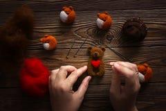 Les mains avec des aiguilles font l'ours avec le coeur de la laine images libres de droits