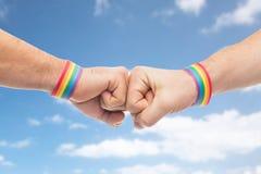 Les mains avec des bracelets de fierté gaie font la bosse de poing Photo stock