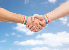 Les mains avec des bracelets de fierté gaie font la poignée de main Photographie stock libre de droits