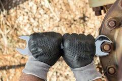 Les mains avec des gants de travail tenant une clé et serrent très Rusty Bolts images libres de droits