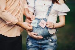 Les mains avec la femme enceinte de cartes de GARÇON et de FILLE se gonflent Photo stock