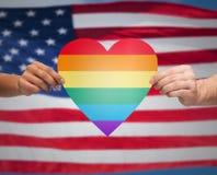 Les mains avec le coeur d'arc-en-ciel forment au-dessus du drapeau américain Photo stock