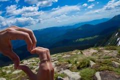 Les mains avec le coeur se connectent le fond de montagnes Concept d'amour Images stock