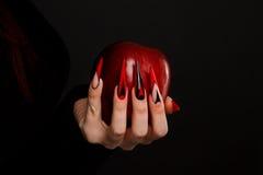 Les mains avec les ongles effrayants manicure la pomme rouge empoisonnée par participation image stock