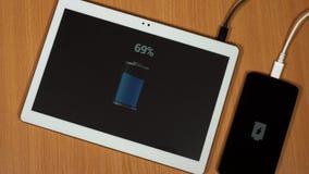 Les mains branchent le chargeur de fil pour téléphoner et marquer sur tablette et mettre dessus la table banque de vidéos
