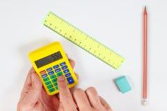 Les mains calculent utilisant une calculatrice au-dessus du lieu de travail de l'ingénieur photographie stock